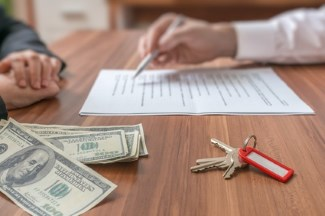 agent reviewing offer with buyer, pile of money